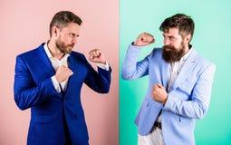 Partnersconcurrenten of bureaucollega's in kostuums met gespannen gezichten klaar te vechten Vijandig of twistziek royalty-vrije stock foto
