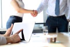 Partnershandenschudden over bedrijfsvoorwerpen op werkplaats Onderneemster die met digitale tablet werkt royalty-vrije stock foto's