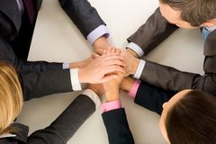 Partnership. Image of business people keeping hands on top of each other at workplace royalty free stock photography
