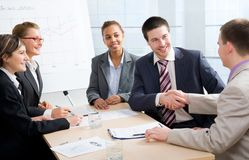 Partnership. Businessmen joining hands in an office Royalty Free Stock Images