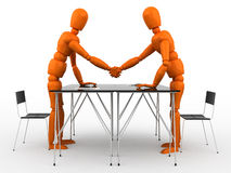 Partnership. Two orange mannequin shaking hands over a desk Stock Photos
