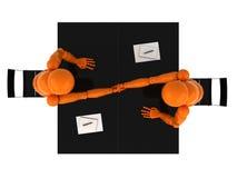 Partnership. Two orange mannequins shaking hands over a desk Stock Image
