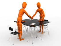 Partnership. Two orange mannequins shaking hands over a desk Stock Images