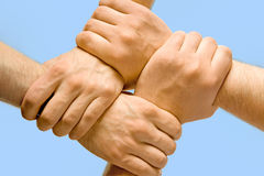 Partnership. Image of crossed hands isolated over blue background