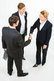 Partnership. Image of successful partners shaking hands in the white room Stock Photos