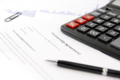 Partnership agreement. Over business desk, closeup, calculator and pen Royalty Free Stock Photo