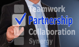 Partnership choice. Touch screen with options 'Teamwork, Collaboration, Synergy and Partnership' and with a smart businessman touching the partnership choice royalty free stock photo