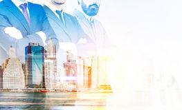 Partnership concept. With businespeople crossing arms on New York city background with sunlight. Double exposure Royalty Free Stock Images