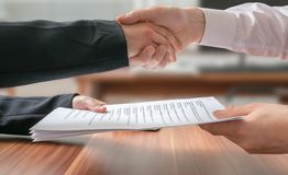 Partnership concept. Business man and woman shaking hands and passing agreement. On blurred background Stock Photos