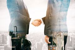 Partnership concept. Businessmen shaking hands on city background. Double exposure. Partnership concept Stock Photography