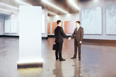 Partnership concept. Businessmen shaking hands in concrete museum with blank banner. Mock up, 3D Rendering. Partnership concept Stock Images