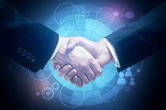 Partnership concept. Close up of handshake on blue background with digital business icons. Partnership concept Stock Photos