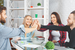 Partnership concept. Happy male and female friends hi-fiving each other at workplace. Partnership concept Stock Photography