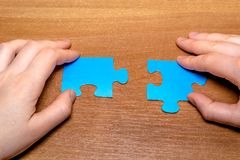 Partnership concept with puzzle pieces and hands together on wooden background stock image
