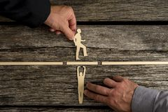 Partnership concept. Using paper cut outs of men with one holding up a bridge in a gap so that the other can walk across over rustic wooden background stock image