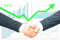 Partnership and financial growth concept. Close up of handshake on creative business report and green upward arrow background. Partnership and financial growth Royalty Free Stock Images