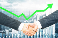 Partnership and financial growth concept. Close up of handshake on creative city and business chart background. Partnership and financial growth concept Stock Photo