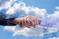 Partnership handshake of a businessman and a doctor . Partnership handshake of a businessman and a doctor on a background of clouds Royalty Free Stock Image
