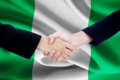 Partnership handshake with flag of Nigeria Royalty Free Stock Image