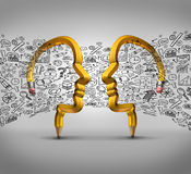 Partnership Ideas. Business concept as two pencils shaped as human heads with financial icons flowing between the partners as a success metaphor for team Royalty Free Stock Photography