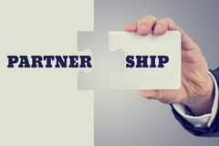 Partnership. Retro image of male hand holding piece of puzzle to create a word Partnership. Concept of importance of teamwork and cooperation Stock Photos