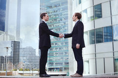 Partnership. Two businessman on office buildings background Royalty Free Stock Photos