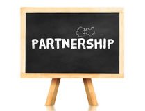 Partnership word and jigsaw icon on blackboard with easel and re Stock Photography