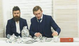Partnery biznesowi, biznesmeni przy spotkaniem w biurze Brodaty szef i kolega z słojem gotówka Kolegów zbierać Obrazy Royalty Free