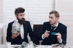 Partnery biznesowi, biznesmeni przy spotkaniem w biurze Kierownik z brodą i kolega z słojem gotówka i karta Obrazy Stock
