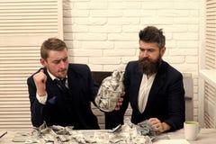 Partnery biznesowi, biznesmeni przy spotkaniem w biurze Koledzy na thoughtfull stawiają czoło z słojem gotówka pełno Gotówka i Obrazy Stock