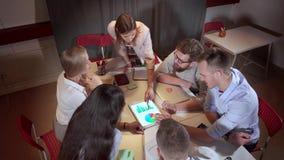 Partnery biznesowi dyskutują sprzedaże firma w nadgodzinowym spotkaniu w biurze zbiory