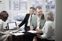 Partnery biznesowi dyskutuje kontraktacyjnych terminy w biurze fotografia stock