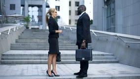 Partnery biznesowi dyskutuje korporacyjnych zagadnienia, rozmowa blisko biura centrum zdjęcie royalty free