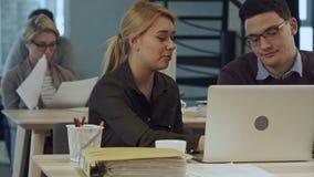 Partnery biznesowi pracuje na laptopie przy nowożytnym biurem zdjęcie wideo