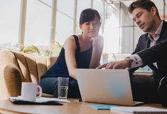 Partnery biznesowi pracuje wpólnie na laptopie w biurze Obraz Stock