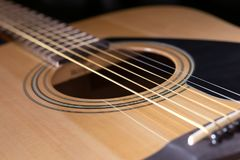 Parts of acoustic guitar close-up. Close-up of rosette and strings of the acoustic guitar on black background Royalty Free Stock Photos