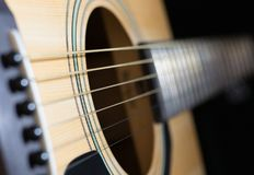 Parts of acoustic guitar close-up. Close-up of rosette and strings of the acoustic guitar on black background Stock Images