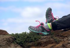 Parts of the body. Legs in bright sneakers on a mountain against the background of blue sky and clouds. royalty free stock photos