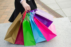 Parts of body of young woman with gift bags Stock Photo