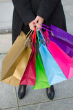 Parts of body of young woman with gift bags Stock Photos