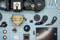 Parts old retro film SLR camera on graph paper. Parts are completely disassembled old retro film SLR camera on graph paper, close-up Royalty Free Stock Photos