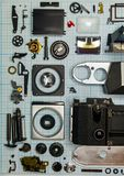 Parts old retro film SLR camera on graph paper. Parts are completely disassembled old retro film SLR camera on graph paper, close-up Royalty Free Stock Photo