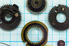 Parts old retro film SLR camera on graph paper. Parts are completely disassembled old retro film SLR camera on graph paper, close-up Royalty Free Stock Photography