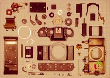 Parts old retro film SLR camera on graph paper. Parts are completely disassembled old retro film SLR camera on graph paper, close-up, toned Stock Images