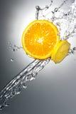 Parts de citron avec l'éclaboussure de l'eau Photographie stock libre de droits
