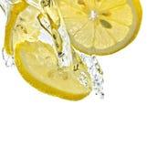 Parts de citron dans l'éclaboussure de l'eau photographie stock libre de droits
