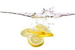 Parts de citron dans l'eau Photographie stock libre de droits