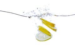 Parts de citron dans l'eau Photo libre de droits