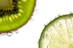 Parts de citron et de kiwi avec des bulles Image stock