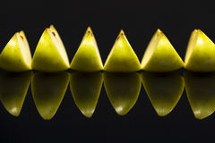 Parts des pommes vertes fraîches sur le fond noir. Images libres de droits